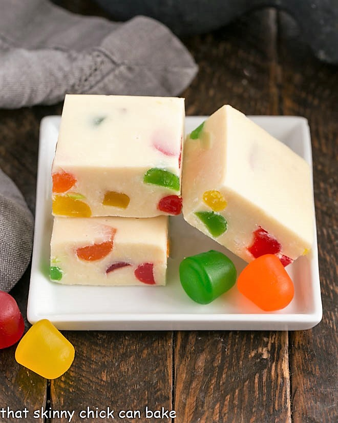 3 cubes of festive white chocolate fudge on a square white plate garnished with gumdrops