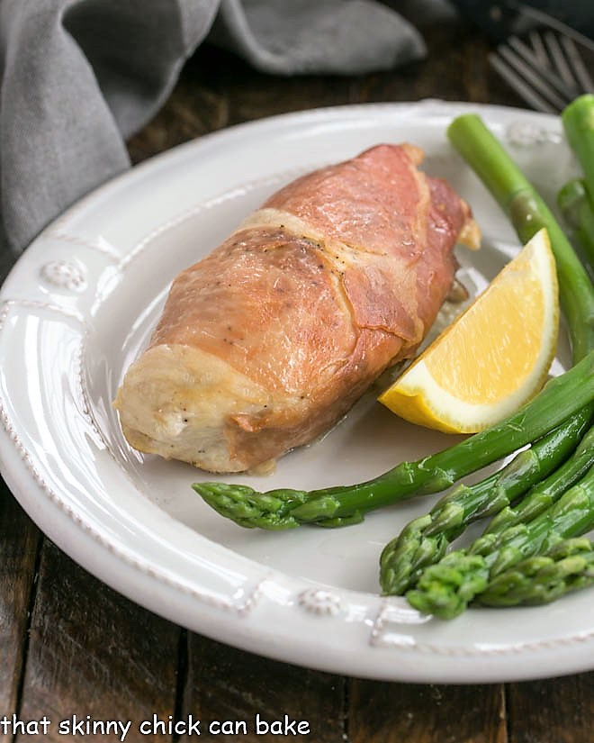 Boursin Chicken on a white plate with a lemon wedge and asparagus