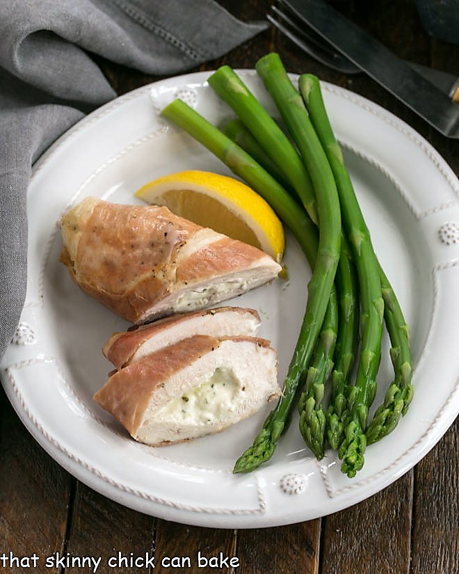 Overhead view of Boursin chicken slices a lemon and asparagus on a white dinner plate