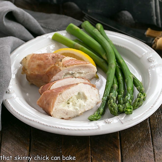 Bousin chicken breast sliced on a white plate with aspargus spears
